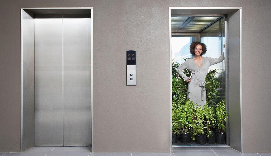 Dos puertas de un elevador, una cerrada y la otra abierta con una mujer rodeada de plantas