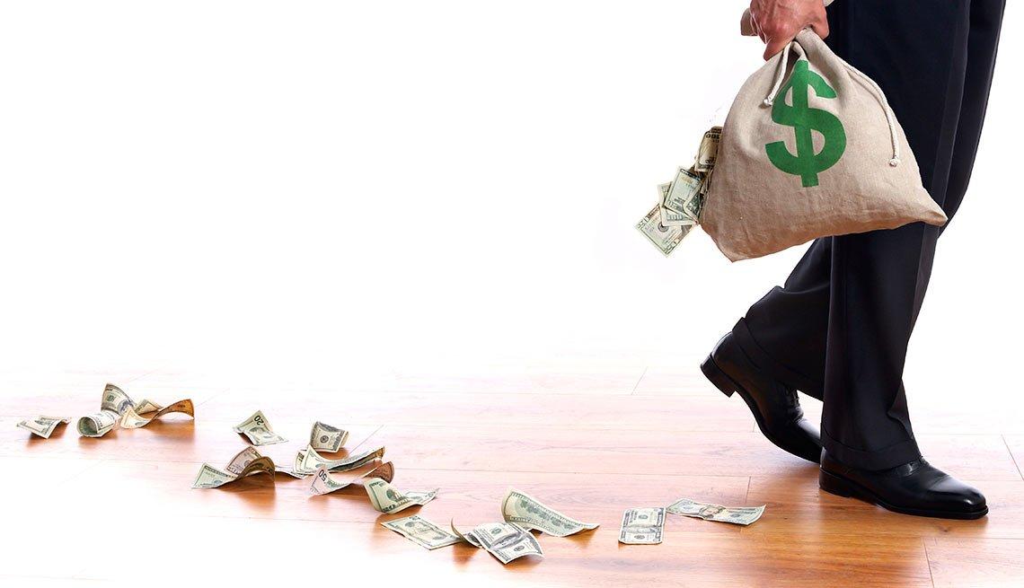 Pies de un hombre y una mano que sostiene una bolsa con dinero que se va regando en un piso de madera