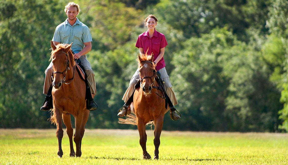 Pareja montando a caballo en un bosque