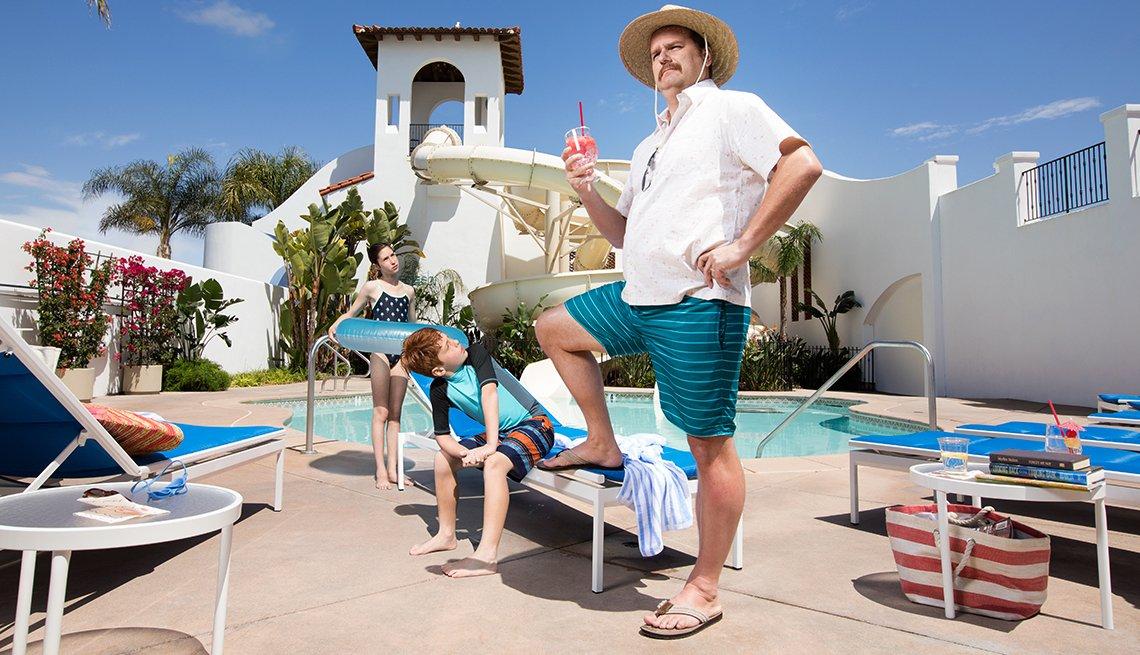 Un hombre con dos niños y una piscina al fondo disfrutando de unas vacaciones, porque ha ahorrado para la jubilación.