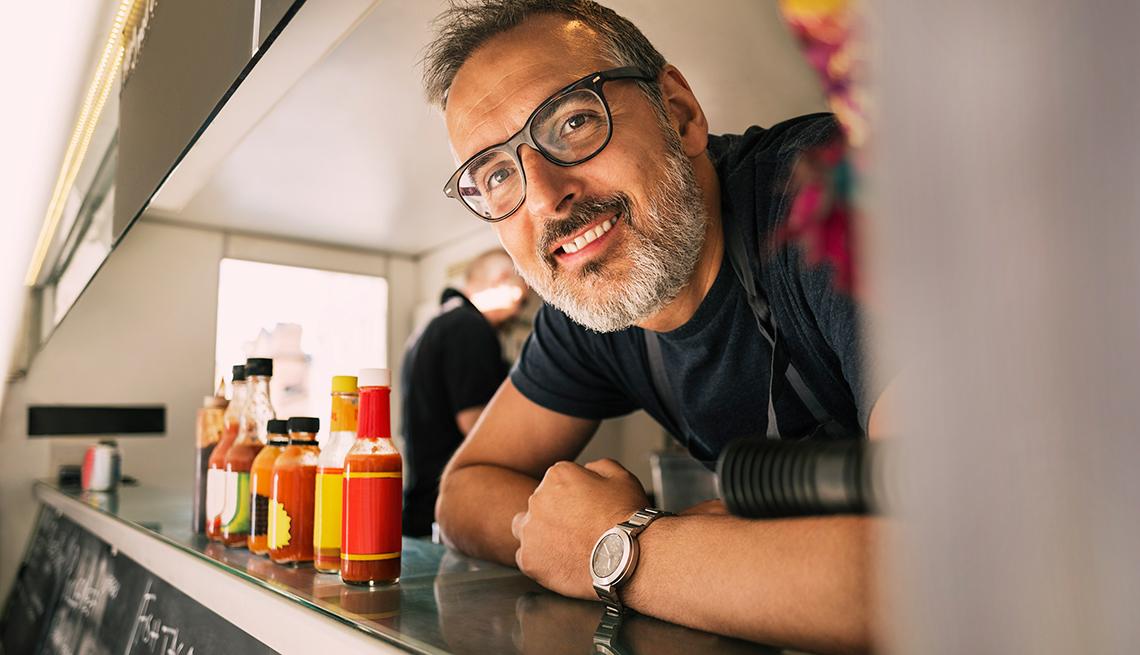 Hombre sonriendo dentro de un camión de comida