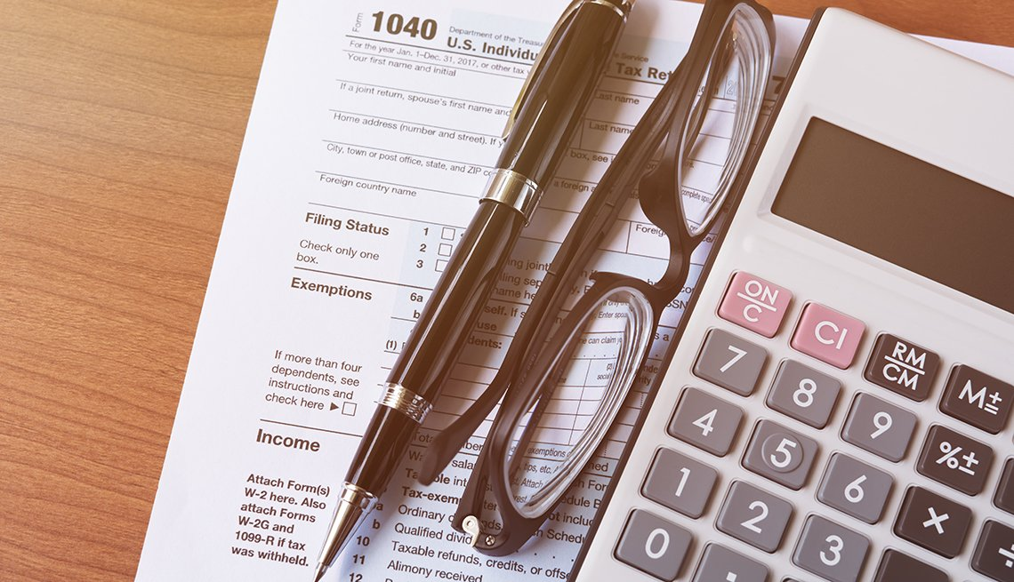 calculator pen and glasses on top of tax form
