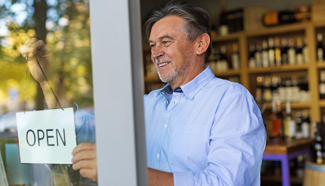 Hombre mayor coloca letrero de abierto en su tienda de vinos.
