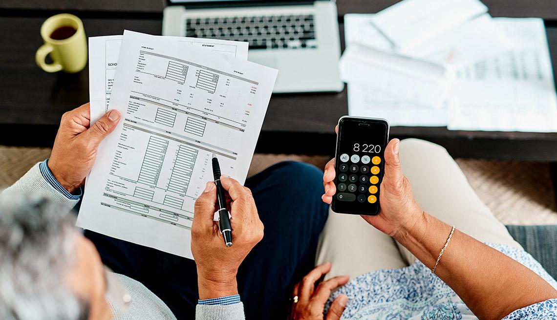 Pajera revisando cuentas de una factura, y usando la calculadora de un teléfono móvil.
