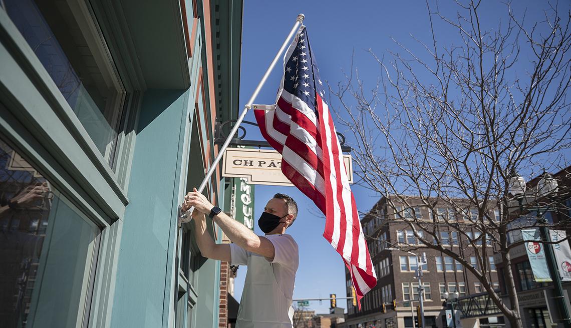 Chris Hanmer colocando una bandera de Estados Unidos a la entrada de su negocio, Ch Patisserie