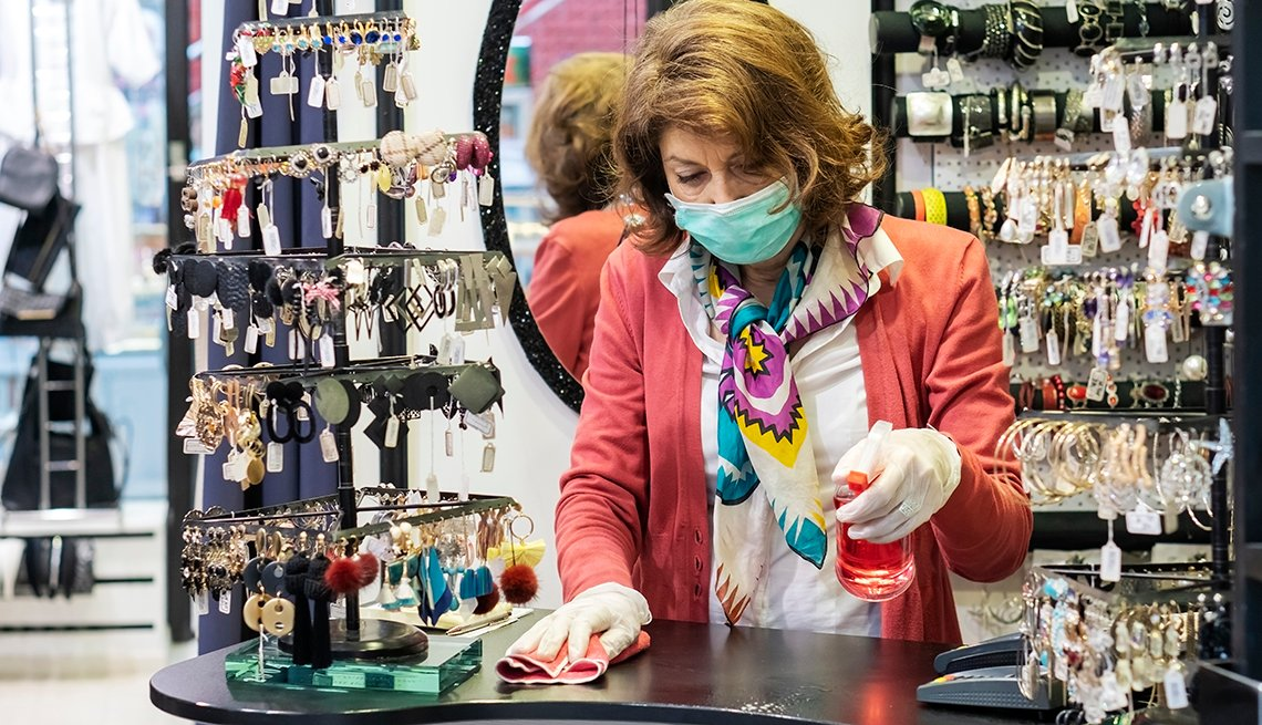 A woman is cleaning the counter of her store while wearing a mask and gloves