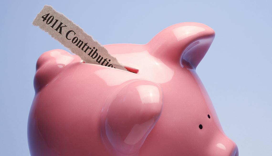 Alcancía en forma de cerdito con un papel que dice en inglés contribuciones para el 401K.