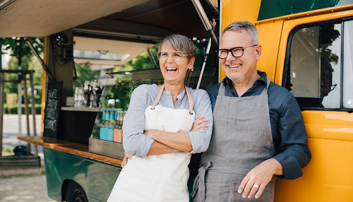A couple stands next to a yellow food truck