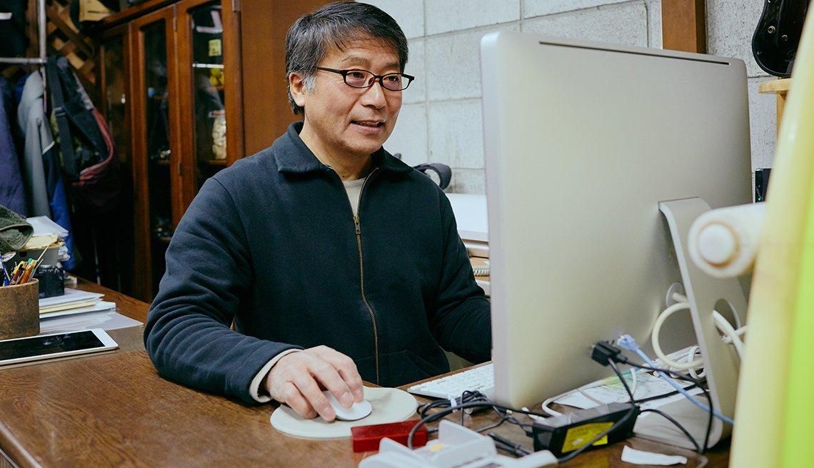 Hombre trabajando frente a una computadora desde su casa