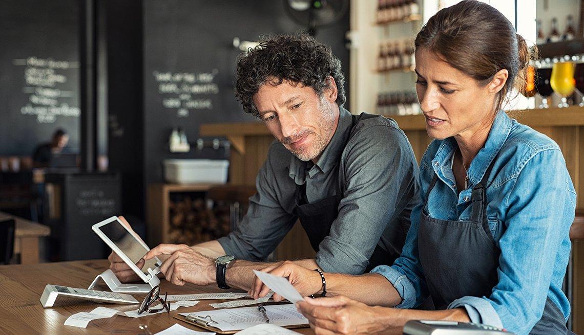 Hombre y mujer revisando las cuentas de su negocio en una de las mesas de su restaurante.