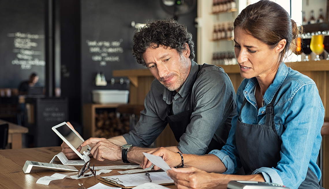 A man and a woman go through financial documents at a table