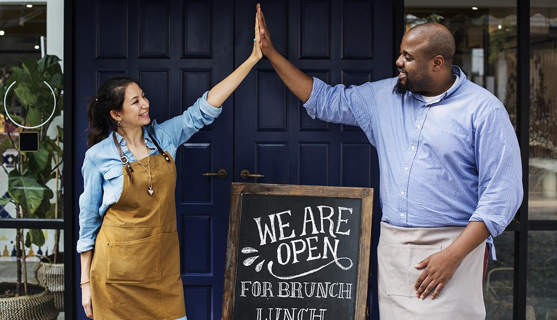 Mujer y hombre que chocan sus manos frente a un negocio
