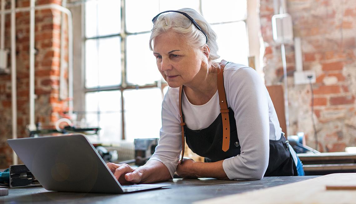 Dueña de negocio mirando su computadora en su local