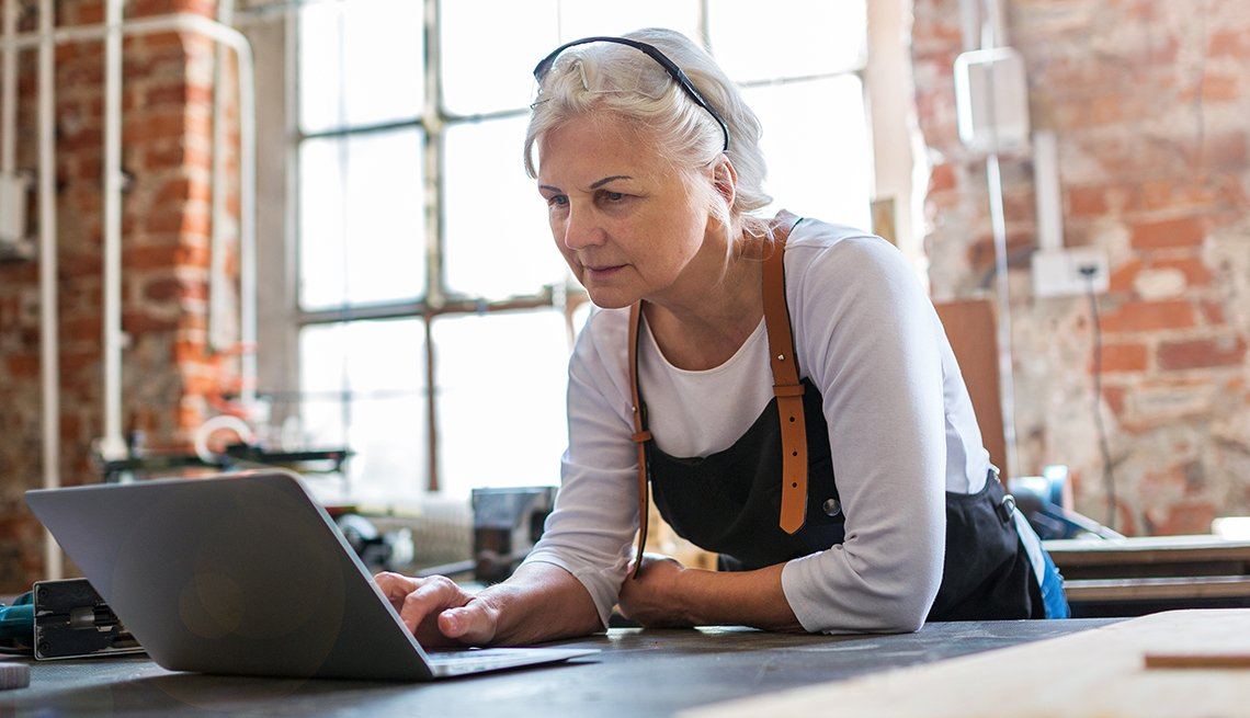 A woman is working on her laptop at her small business