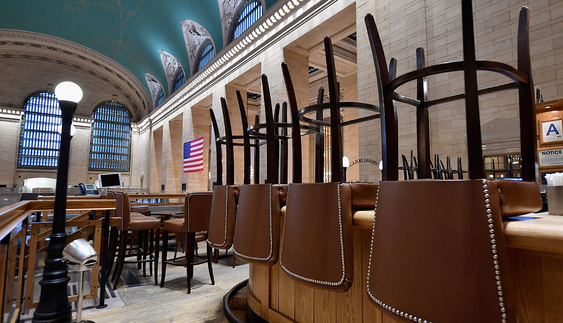 Restaurante vacío con las sillas volteadas sobre las mesas en Grand Central, Nueva York,