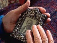 Manos de mujer acariciando la foto enmarcada de un hombre joven - Eligibilidad del seguro social ante la muerte de su pareja