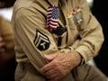 Un veterano de guerra en su uniforme con una bandera de los Estados Unidos