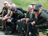Un grupo de hombres sentados en un parque dialogando