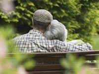 Una pareja de adultos mayores abrazados en un parque