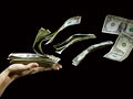 Billetes de dólares flotando de la mano
