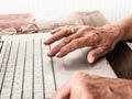 Primer plano de las manos de un hombre mayor con una computadora portátil - Cómo inscribirse para recibir sus depósitos del seguro social