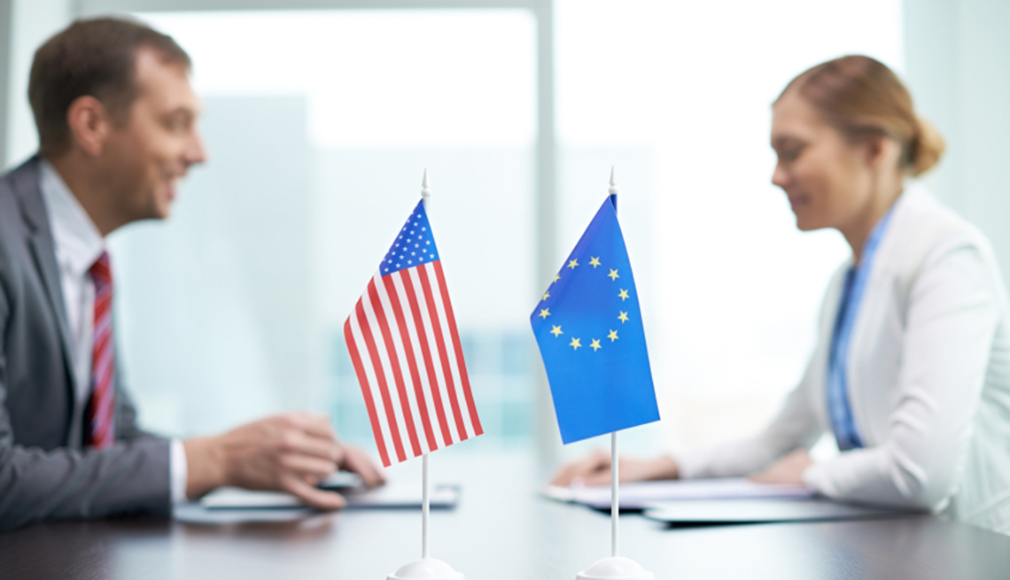 European Unity and American flags and two negotiating people in the background