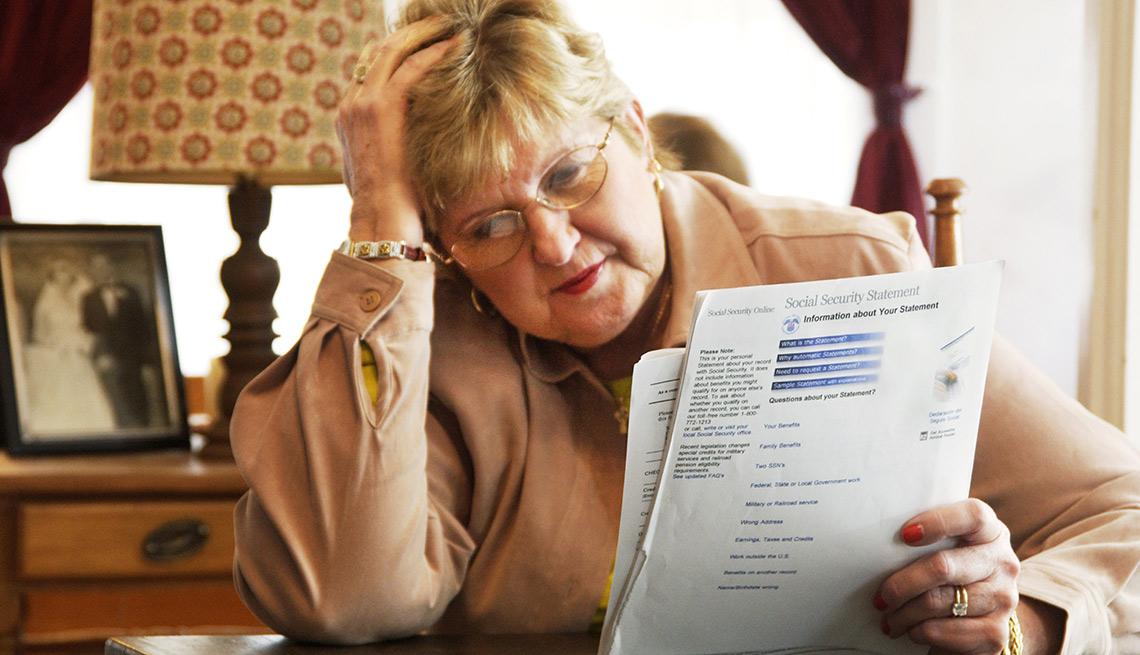 """Señora con la mano en la cabeza mientras revisa unos papeles -  """"Reclamar y suspender"""" estrategia para que solteros maximicen sus beneficios del Seguro Social."""