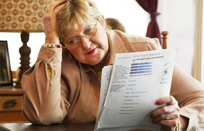 Señora con la mano en la cabeza mientras revisa unos papeles -