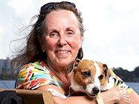 Janet Boes sostiene a su perro - Beneficiados con el Seguro Social