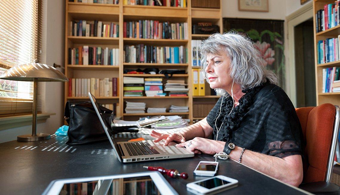 Mujer mayor frente a una computadora personal - Seguro Social y trabajadores independientes.