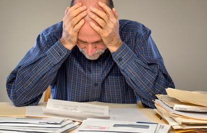 Hombre sentado tocándose la cabeza y apoyado en una mesa con recibos - Qué hacer cuando los pagos del Seguro Social son incorrectos.