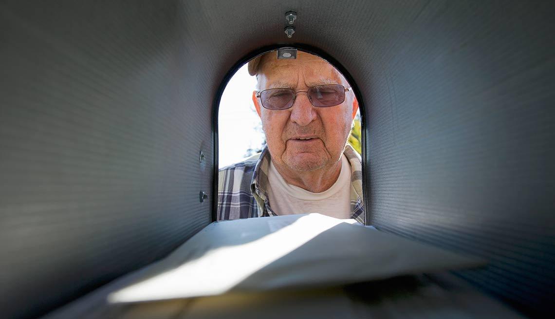 Hombre mayor mirando un buzón de correo