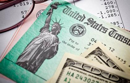 Billetes de 100 dólares y cheque del tesoro encima de un estado de cuenta - Cambios al Seguro Social en el 2016