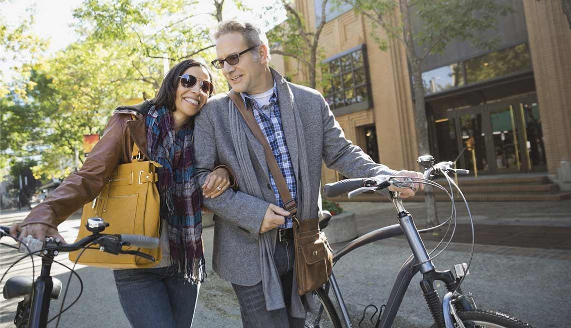 Un hombre y una mujer caminan mientras llevan sus bicicletas en la mano