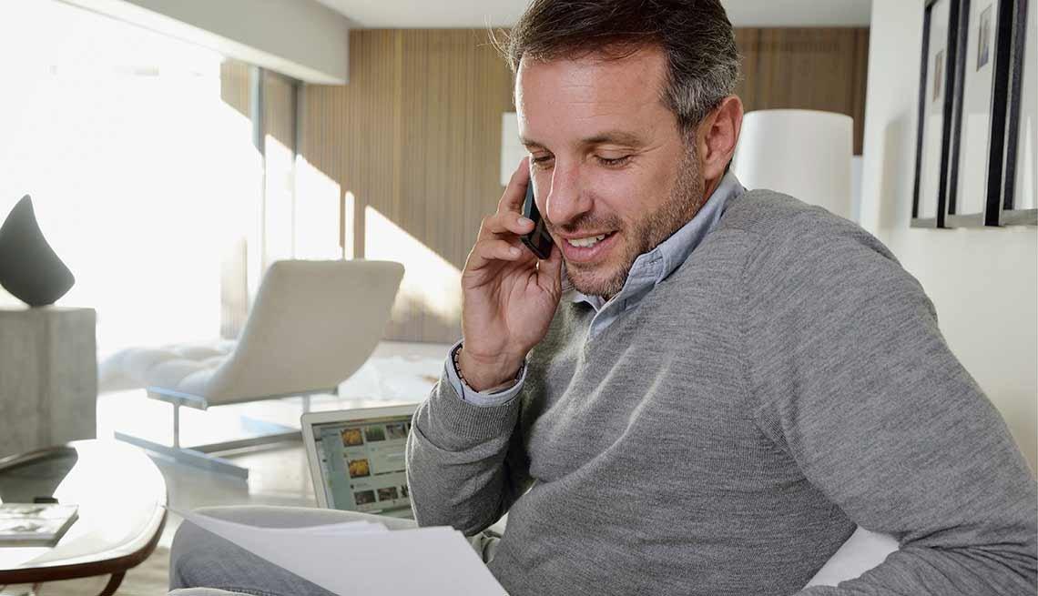 Hombre hablando por teléfono y sentado en un escritorio