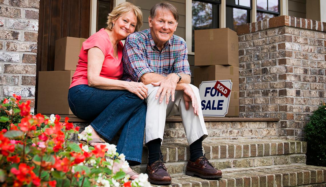 Pareja mayor sentados en la entrada de casa con cajas de mudanza alrededor, para vivir una jubilación solo con los beneficios del Seguro Social