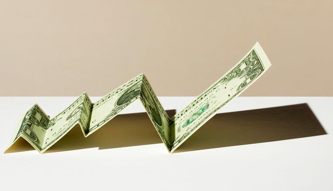 Un dólar doblado en líneas rectas dobladas a manera de gráfica estadística