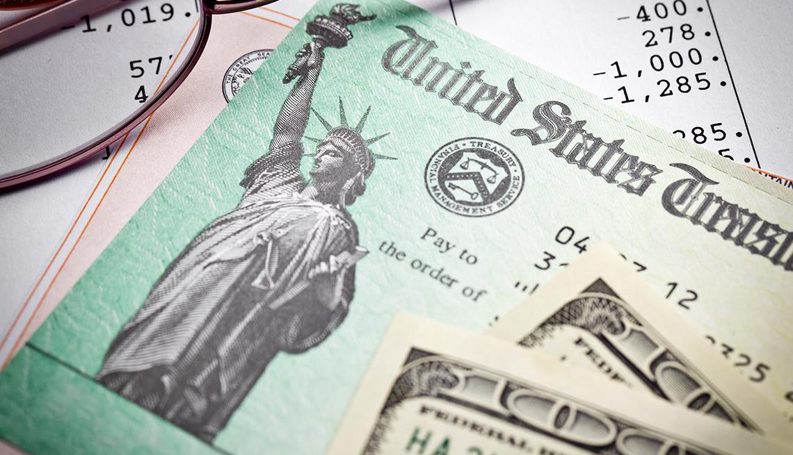 Bonos del tesoro, lentes y un billete de 100 dólares