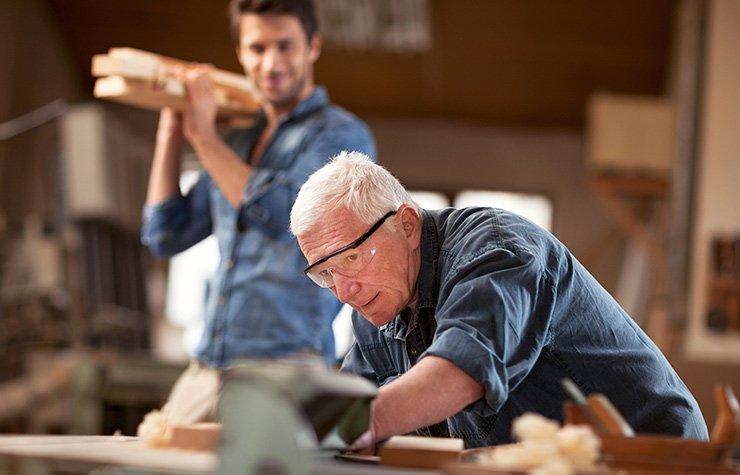 Hombre mayor y hombre joven trabajando en una carpintería