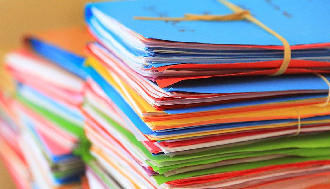 Carpetas de colores con papeles arrumadas una encima de la otra