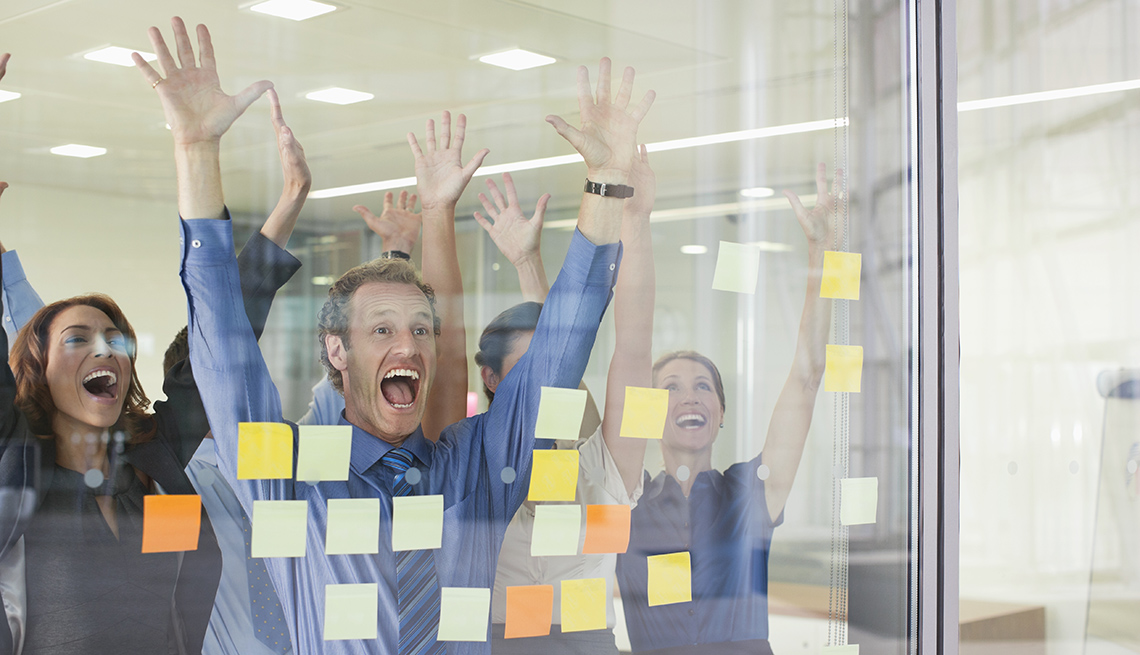 Workers Raise Hands and Shout, Sticky Notes On Glass, Should You Ever Volunteer For a Layoff?