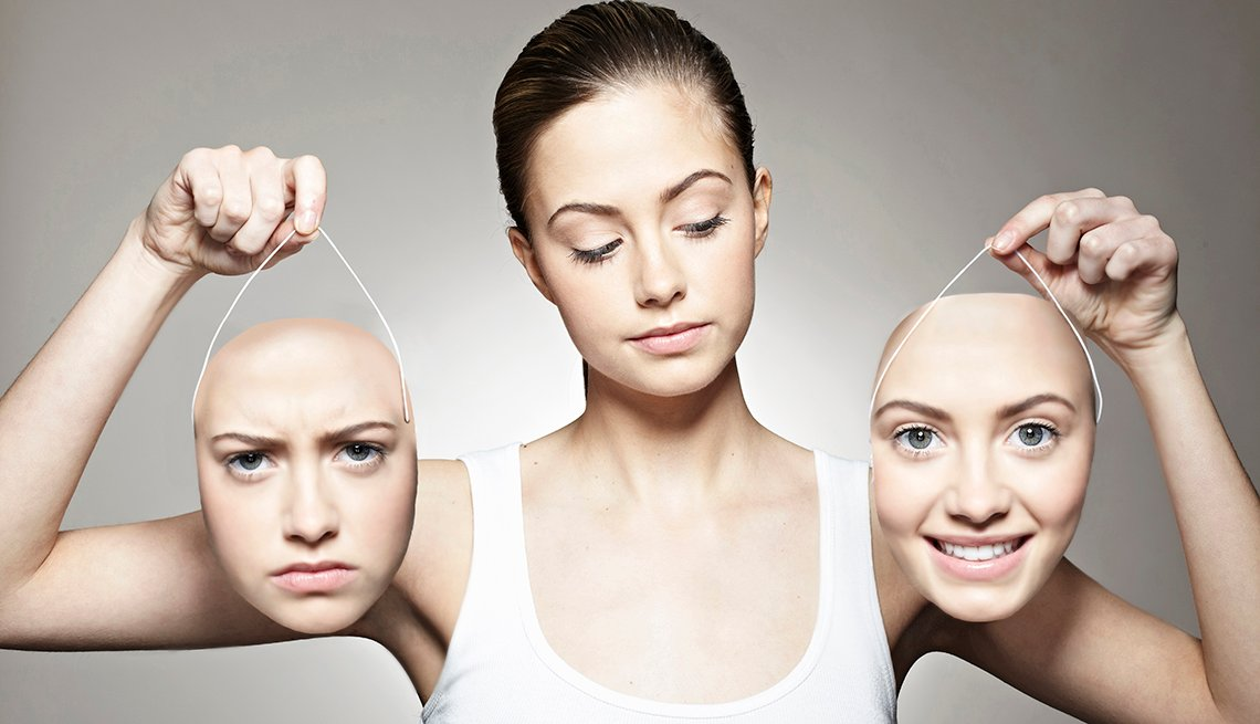 A woman holds two masks of her face with happy and sad expressions