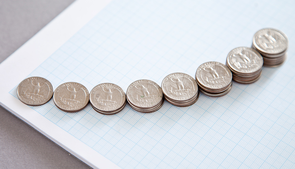 Monedas de 25 centavos apiladas en una curva sobre una hoja de gráficas geométricas