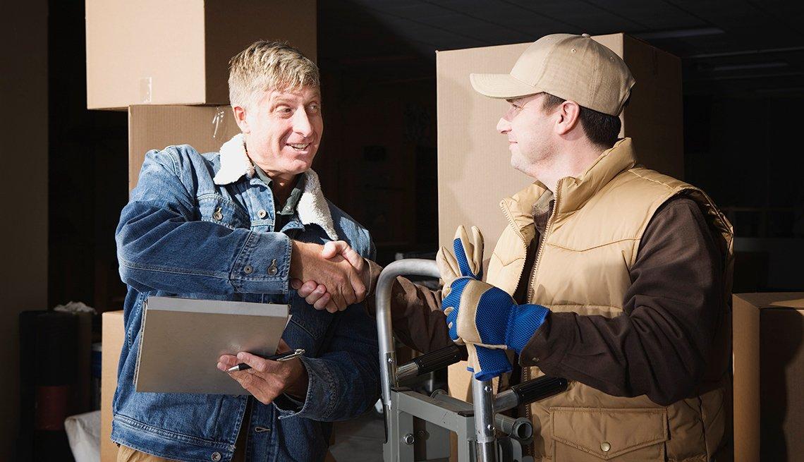 Dos hombres dando un saludo de mano en una bodega