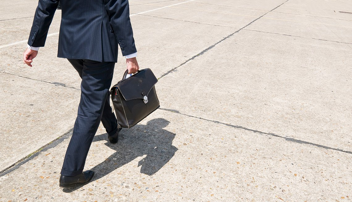 A man in a suit walks with a briefcase