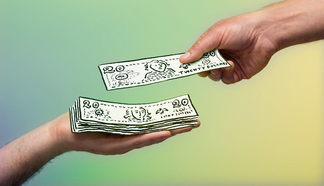 Dos manos sosteniendo billetes de dólar de juguete
