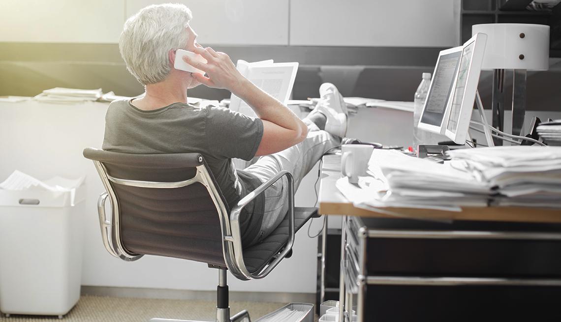 Hombre con ropa informal y poniendo los piés en un escritorio