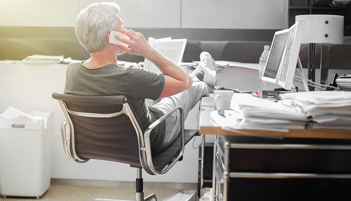 Older adult sitting at an office on his phone