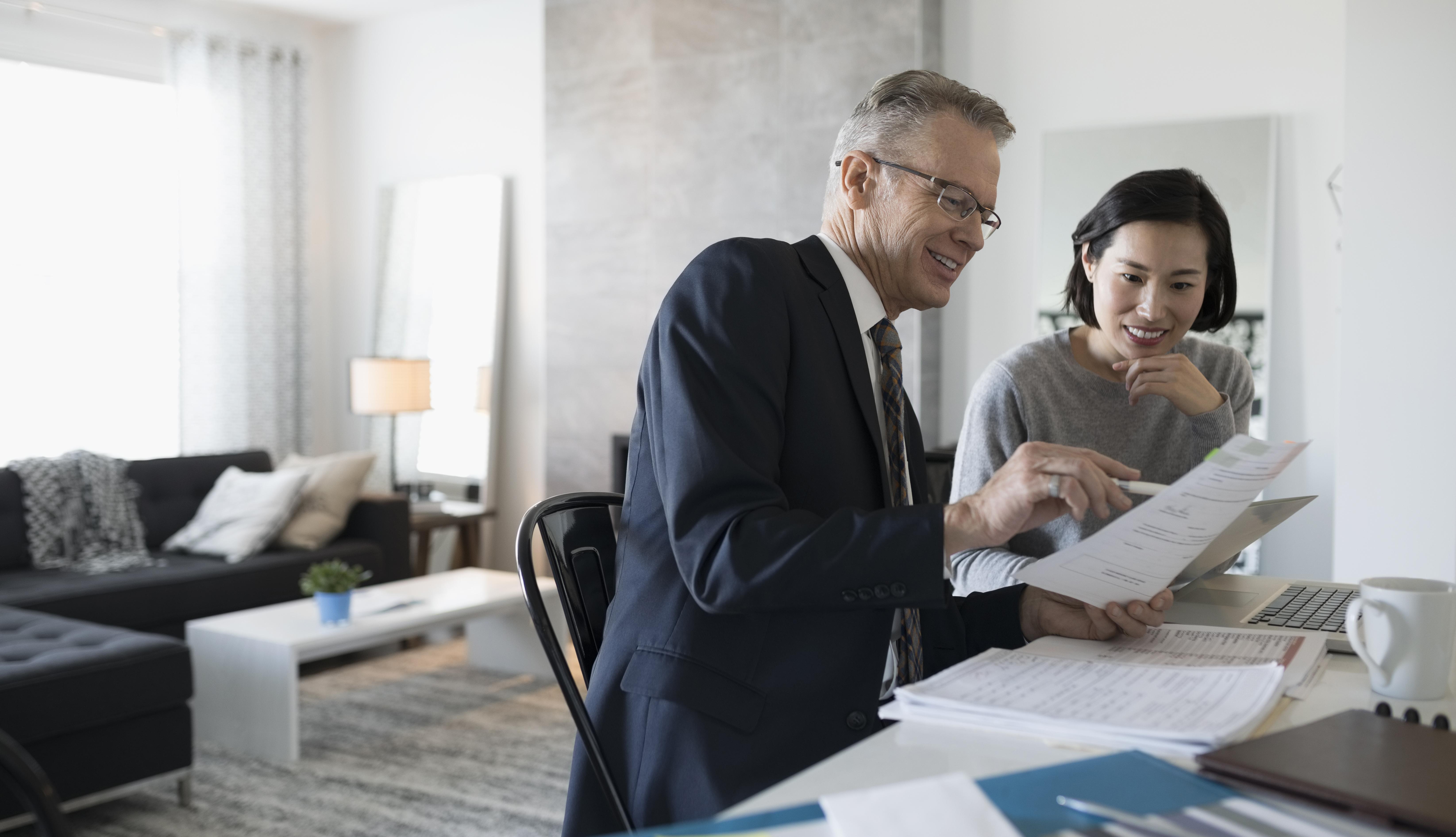 Un asesor financiero se reune con una mujer en su casa.