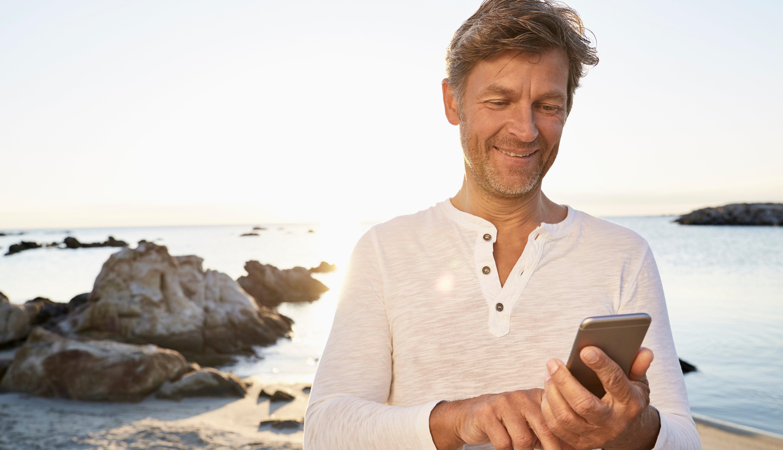 man using smartphone on beach
